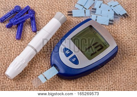 The blood glucose meter on the background of burlap.