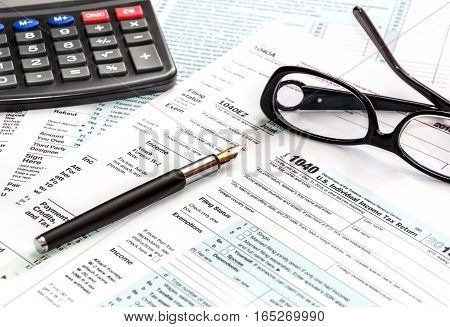 Calculator glasses and pen on tax form 1040.