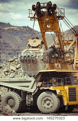 Heavy mining truck and excavator developing the iron ore on the opencast mining site