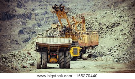 Heavy mining trucks and excavator working on the iron ore opencast mining site