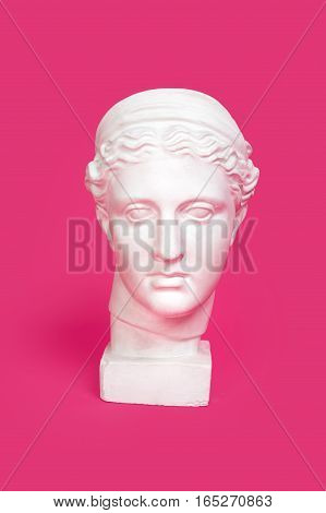 Marble head of young woman, ancient Greek goddess bust isolated on pink background.