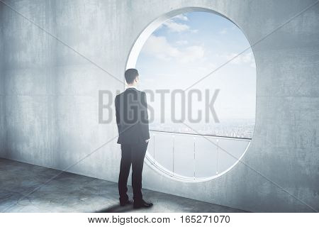 Thoughtful Businessman In Concrete Interior Side