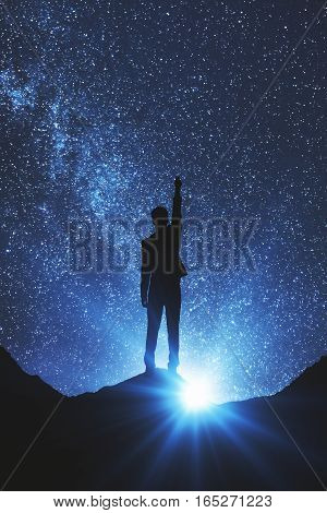 Back view of businessman in space reaching out for the stars. Dreams concept