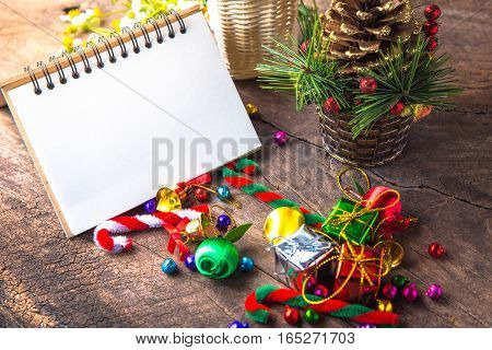 Christmas and new year wooden background banner with blank notebook gift box daisy flower candy ball and cane pine decoration on vintage background.