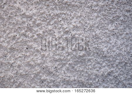 Grey wall with pattern of rough cement plaster