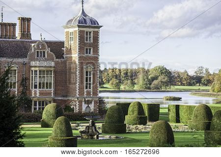 English country estate manor house with ornamental gardens and lake. Period details including dutch gable topiary and water fountain. Rich gentry landscape.