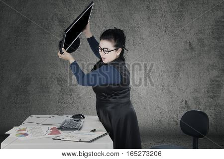 Angry woman throwing her computer with financial crisis chart on the desk