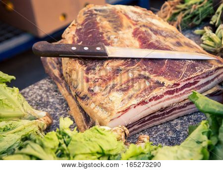 Slab of bacon and a knife at a market in split