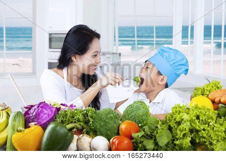 Young Asian woman feeding her son with healthy food and fresh vegetables in the kitchen