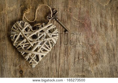 wicker heart handmade with the key lying on a wooden base . top view