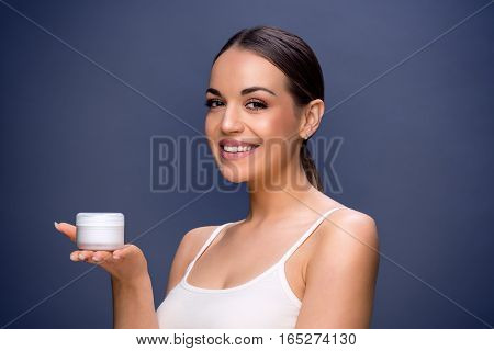 Skincare- Young pretty woman holding cosmetic cream