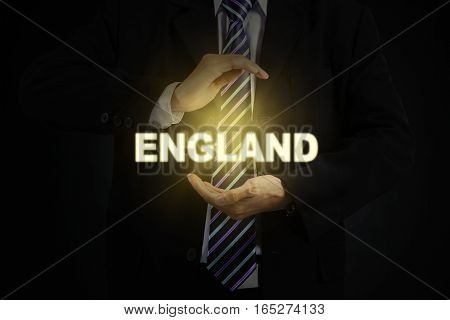 Image of businessman wearing a formal suit while holding a golden word of England