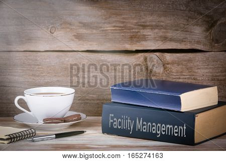 Facility Management. Stack of books on wooden desk.