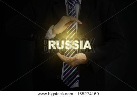 Close up of male entrepreneur wearing formal suit and protecting a bright Russia word
