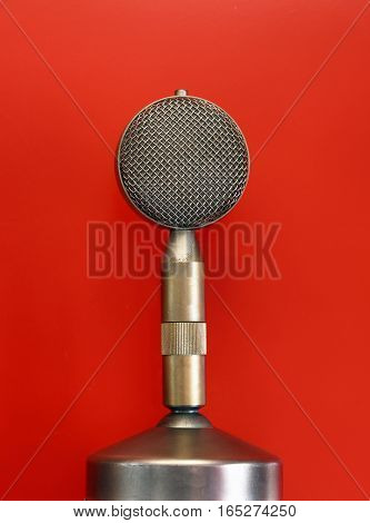 Vintage Metal Microphone Over Red