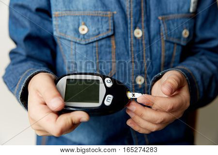 A man hand holding Glucometer for Blood Glucose Testing on wood table, Healthcare and Medical Glucometer Technology background concept