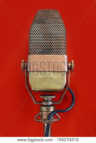 Vintage Metal Microphone Over Red