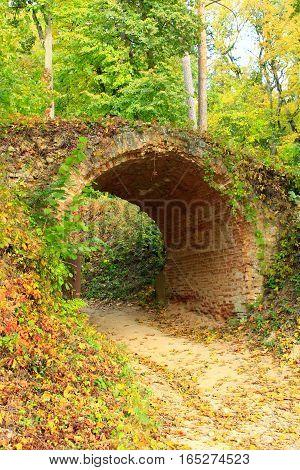 sandy road under historical arch from ed bricks in Kachanivka park