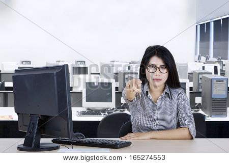 Portrait of a young businesswoman wearing glasses in the office while points her finger at you and looks angry