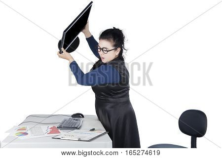 Young businesswoman throwing her computer with financial chart on the desk isolated on white background