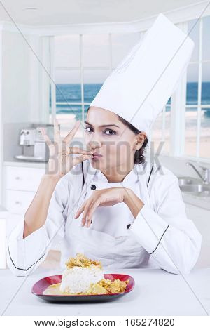 Image of young female chef giving a perfect gesture with hand for delicious food while looking at the camera in the kitchen