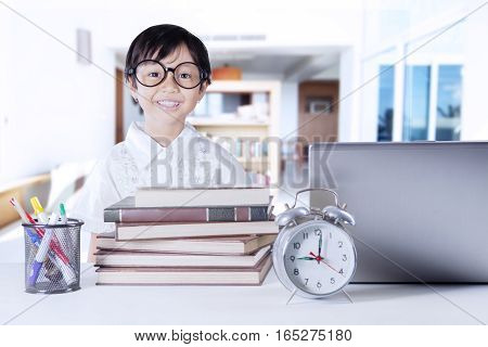 Photo of a cute little girl with science book alarm clock and notebook computer on the table. Shot at home
