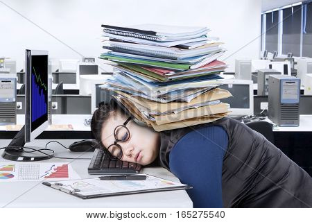 Portrait of female entrepreneur sleeping on the desk with stack of documents over her head