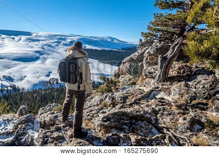 Traveler is standing on the edge of abyss above vast forest territory and winter mountains