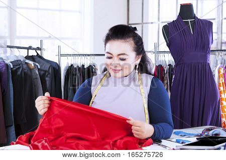 Portrait of a young fashion designer looking at a red textile material at workplace