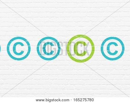 Law concept: row of Painted blue copyright icons around green copyright icon on White Brick wall background