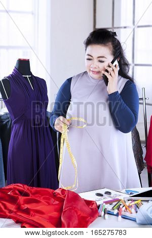 Portrait of a female fashion designer talking on the mobile phone while holding a measuring tape at the workplace