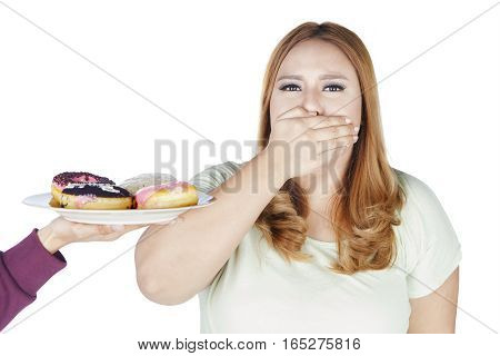 Portrait of fat woman closed her mouth while reject a plate of donuts isolated on white background