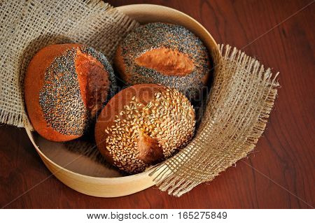 top view on buns with sesame and poppy seeds in burlap basket.