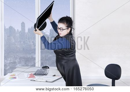Female entrepreneur throws computer with financial chart on the desk winter background on the window