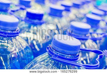 Caps group of blue five liter bottles closeup. Shallow depth of field.