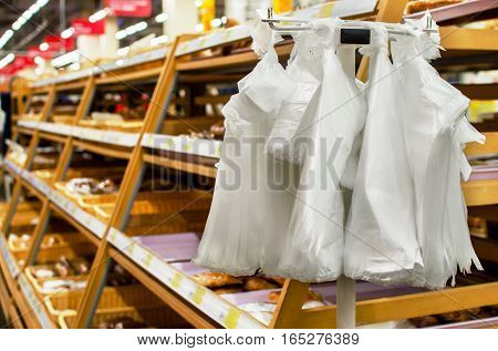 Stand with cellophane plastic bags in the bread department store supermarket.