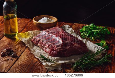 Raw Ribs with Greens and Spices on Wooden Table.
