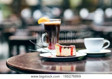 Slice of cheesecake with cherry and cup of tea on wooden background in cafe
