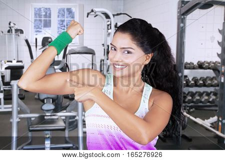 Portrait of indian woman pointing her muscle while standing in fitness center winter background on the window
