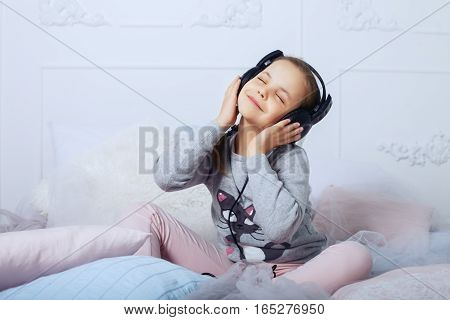 Child girl sitting in headphones and listening to the song. The concept of childhood education and music.