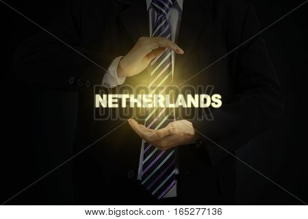 Picture of male entrepreneur wearing formal suit and protecting a light of Netherlands word