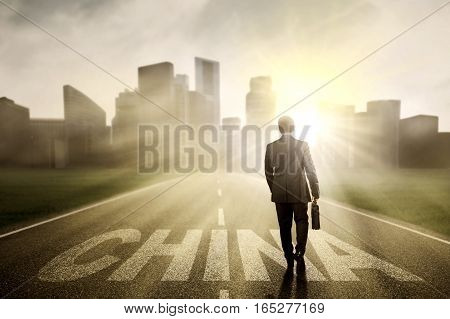 Male entrepreneur walking on the street while carrying a briefcase with China word and sunrise