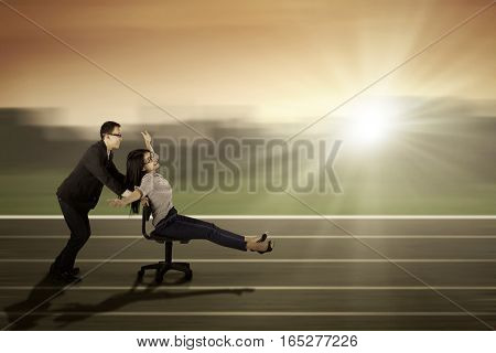 Image of young male manager pushes his partner on the chair to race and compete on the track