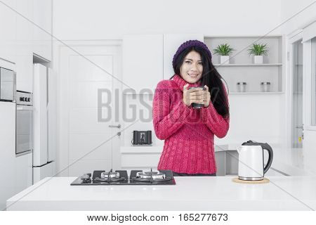 Beautiful young woman smiling at the camera while holding a cup of hot drink and wearing winter clothes in the kitchen