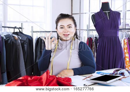 Portrait of professional designer showing ok gesture while smiling at the camera in her workplace