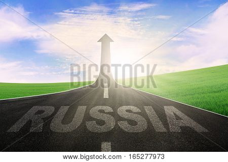Empty road leading to an arrow upward and symbolizing success with a word of Russia on the street