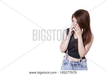 Picture of sad teenage crying alone while covering her face with hand isolated on white background