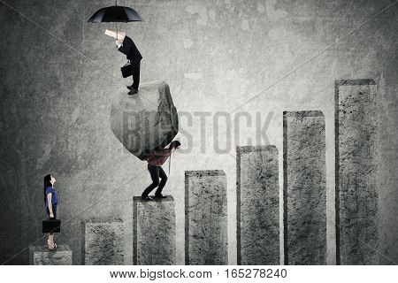 Young businessman walking upward on the graph and carrying his partner with a big stone while a businesswoman following him on the back