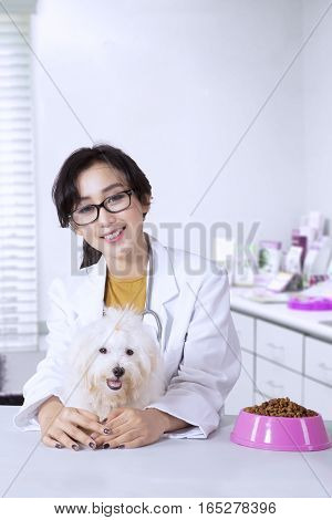 Young veterinarian is embracing dog and sitting in the clinic with a bowl of dog food on the table