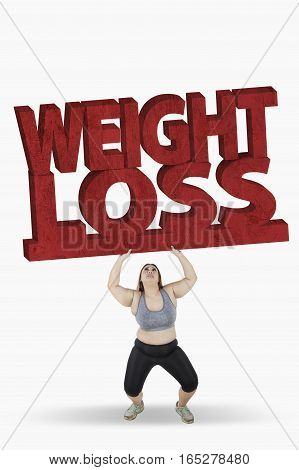 Picture of obese woman lifting a big weight loss word while standing in studio isolated on white background